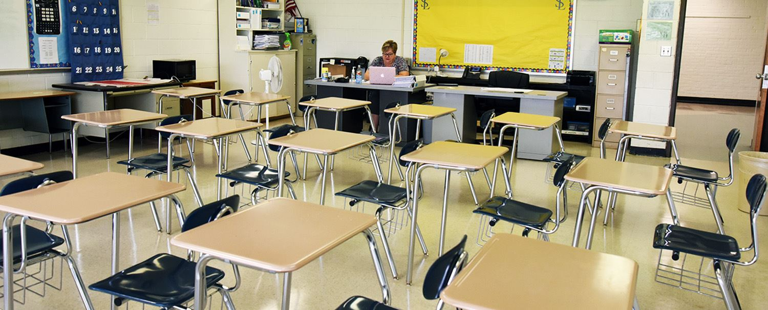 Female teacher sits at her desk in the corner of a classroom of empty desks.