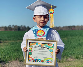 Pre-K student shows certificate of completion