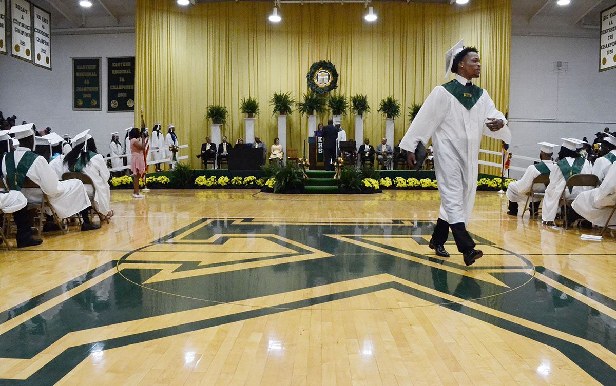 Kinston High students walks across the green 'K' logo on the gym floor after receiving his diplomas