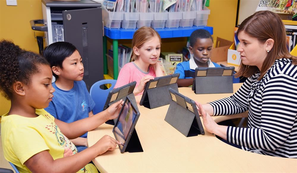 Elementary teacher at table with students and their iPads