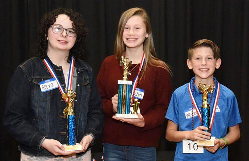 Three students, two girls and boy, pose while holding trophies as spelling bee winners