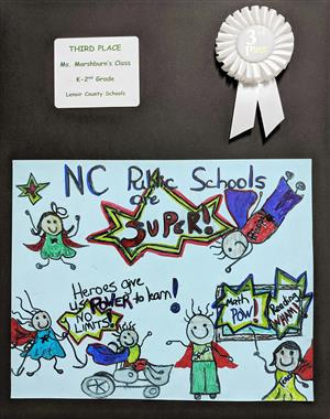 Superheros poster drawn by children mounted on a black board with a white third-place ribbon attached.