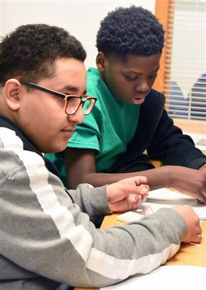 Two middle school males work on a problem dealing with electric circuitry during Science Olympiad