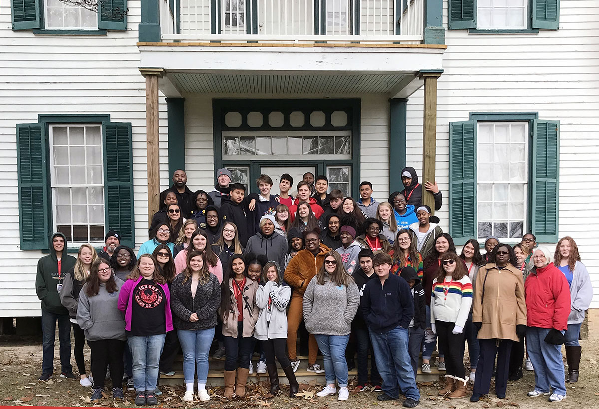 Large group of ninth grade students in winter wear post in front of a restored white 19th century house.
