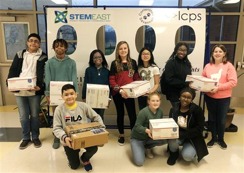 Ten middle school students pose holding parcel post packages.
