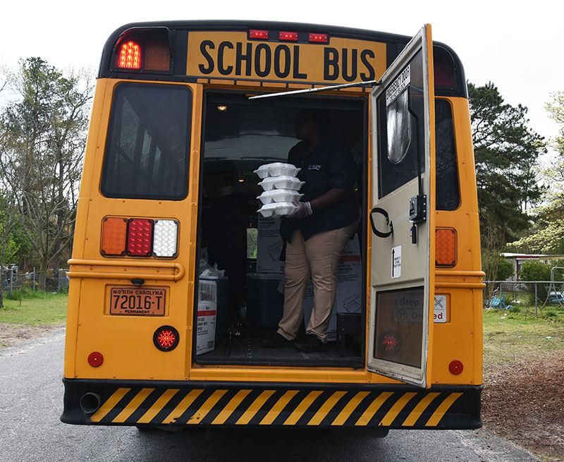 Woman stands in back door of school bus holding Styrofoam food trays.