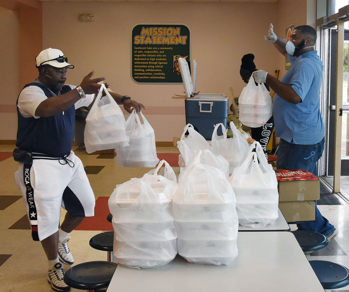 Two men distribute meals in Styrofoam containers.