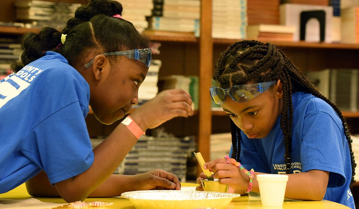 Two elementary students, African American girls, conduct an experiment during Science Olympiad.