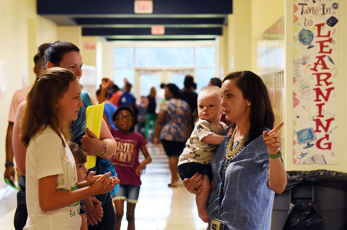 Teacher points as she directs a family to classroom location during orientation in 2018.