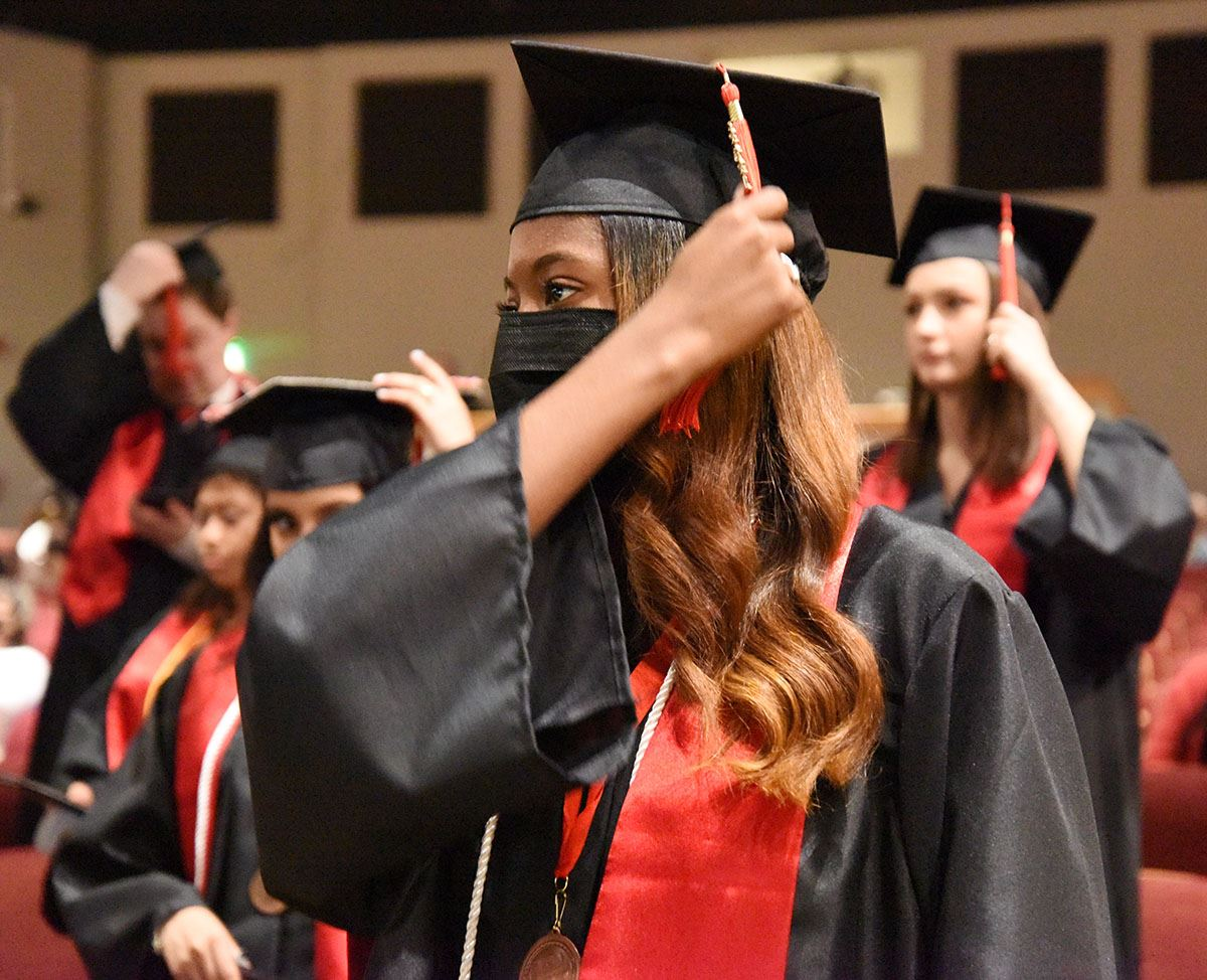Female high school senior in black cap and gown turns tassel.