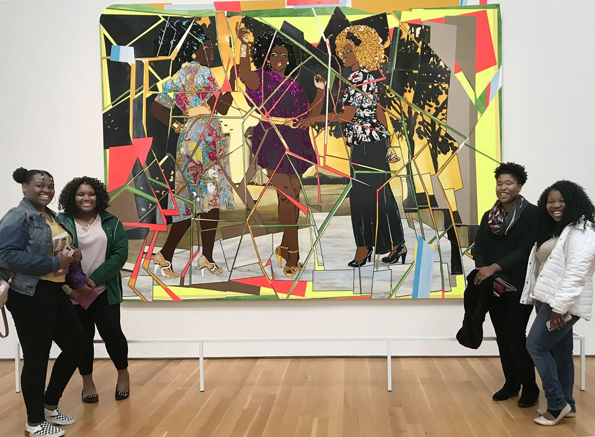 Four students pose with painting at art museum.