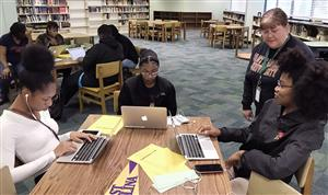 Female school counselor stands over 3 students working on laptops in school library.