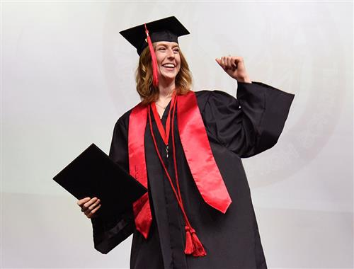Female student gives a fist pump as she exits stage after receiving her diploma