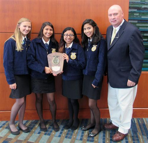 Four girls on the team pose with first-place plaque with team advisor.