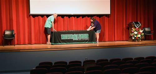 Man and woman on high school auditorium stage adjust cloth on table.