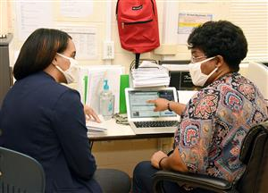 Two African American women seated beside each other at desk talk and wearing mask talk as one points to a laptop screen.