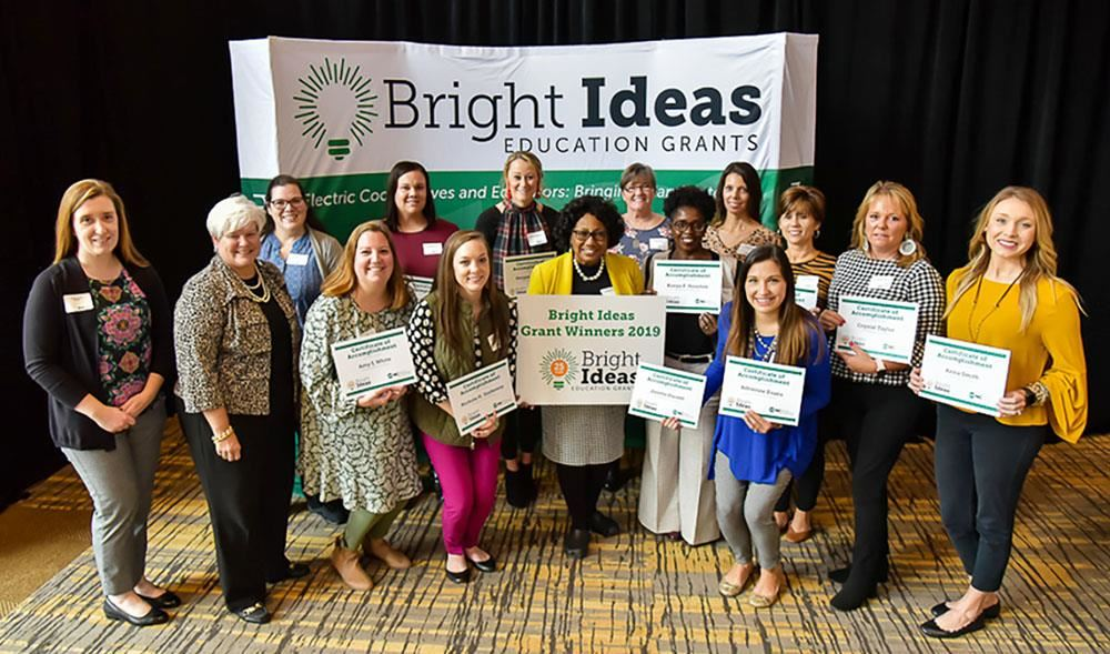 Fourteen women holding certificates pose in front of a Bright Ideas grants banner.