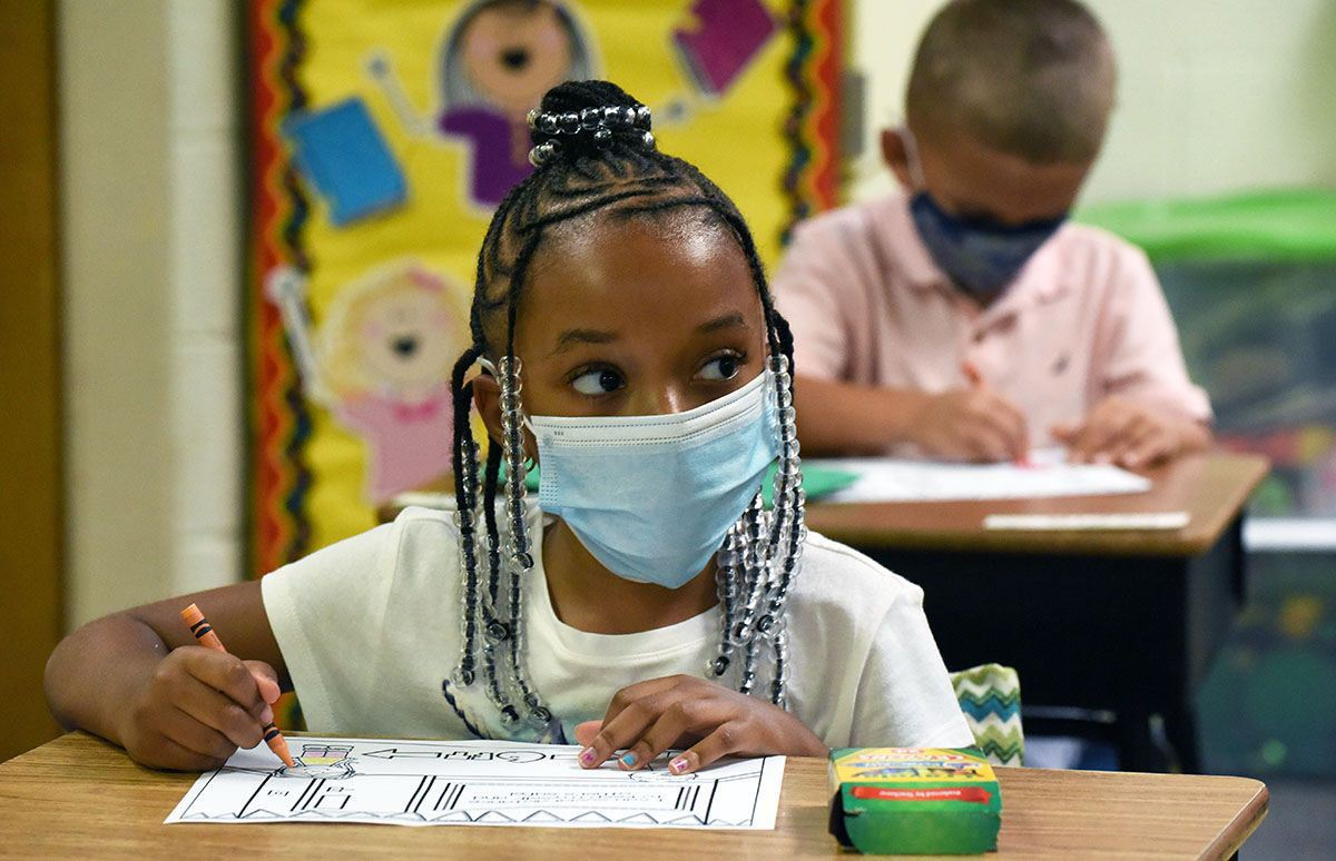 Female African American child wearing face mask colors at her school desk.
