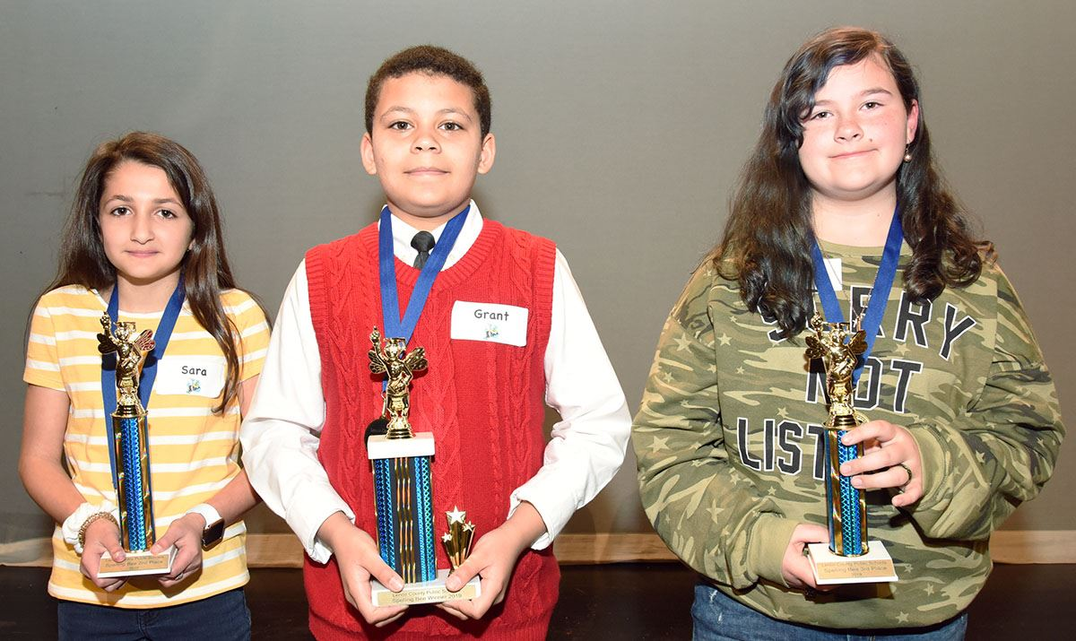 First, second and third place winner in the 2019 spelling bee hold trophies.