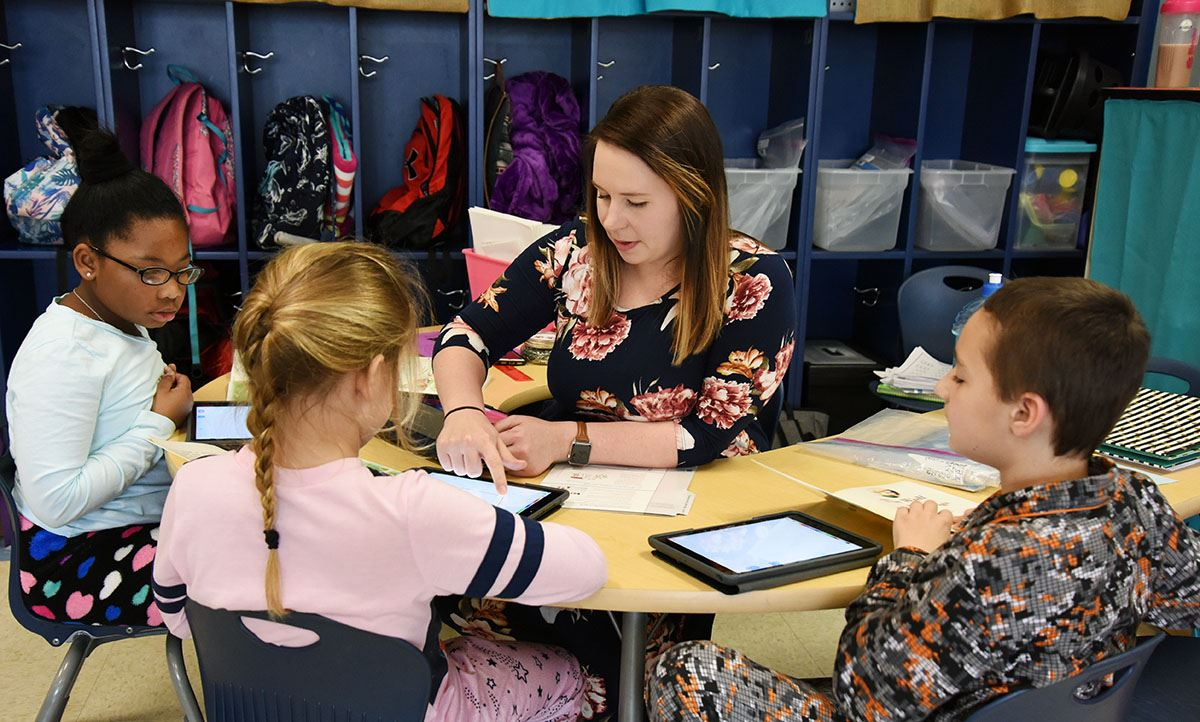 Teacher works with three students on iPads during Digital Learning Day