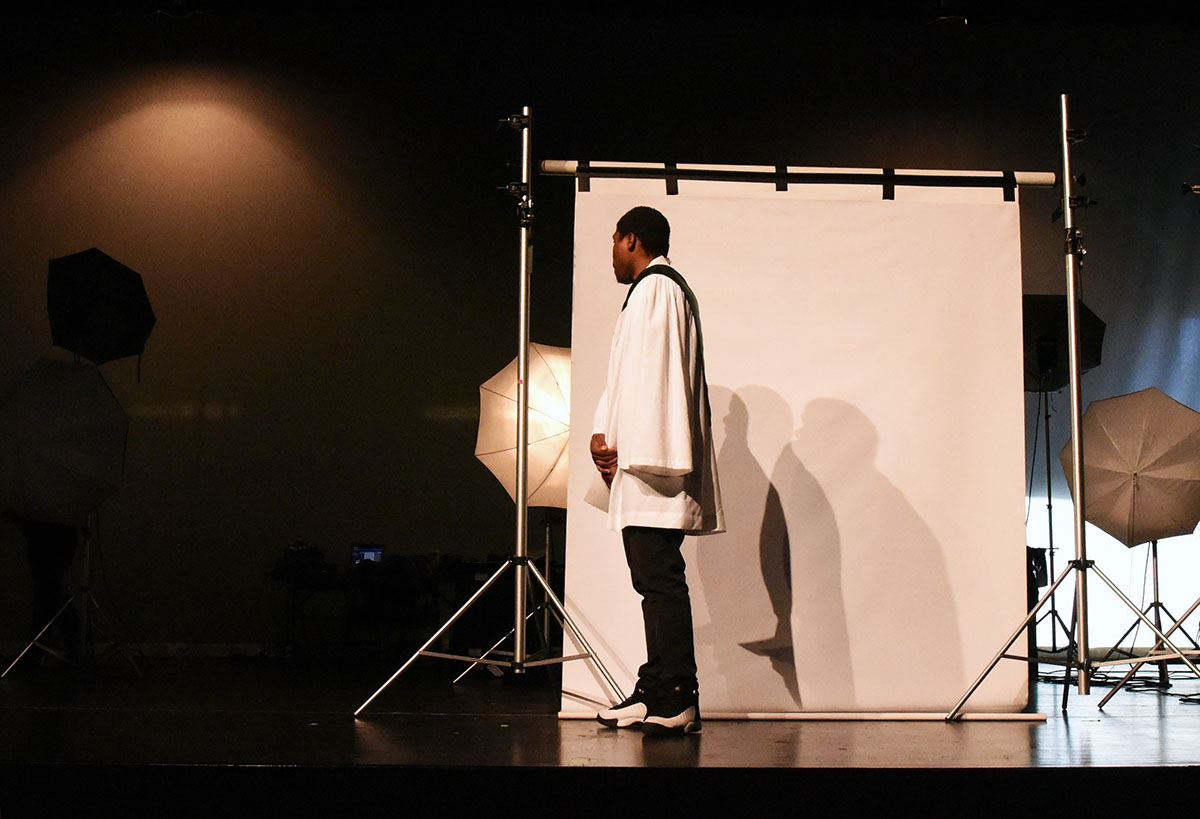 Male student stands in front of a white screen while waiting to have his graduation photo taken.