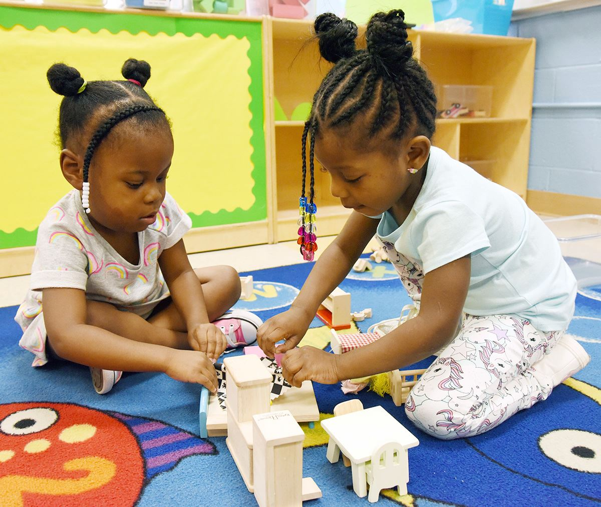 Two 4-year-old African American girls play with blocks on the floor.