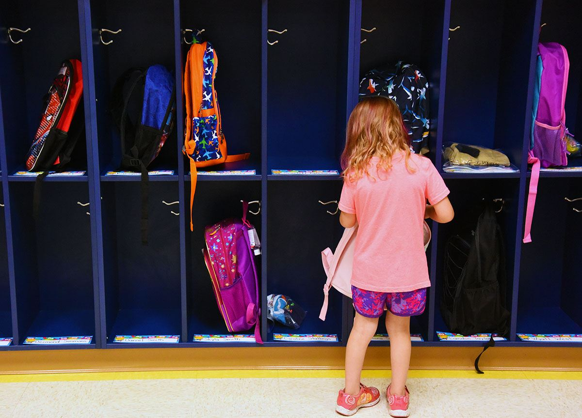 Female kindergarten students stands with back to camera in front of classroom cubbies.