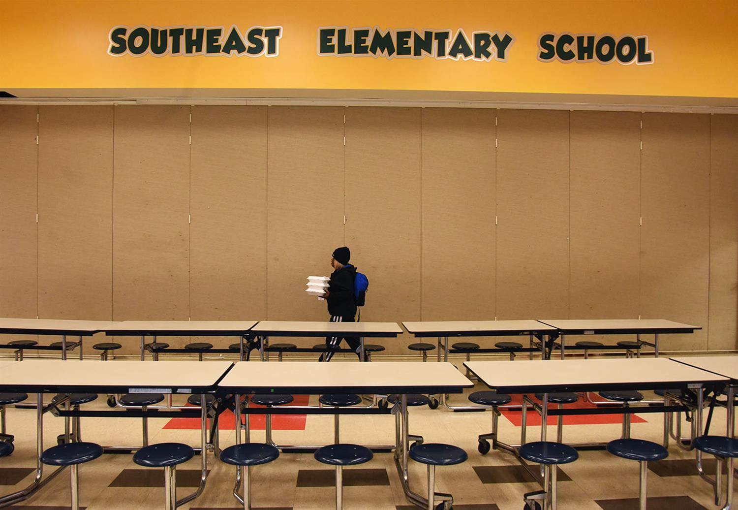 Woman walks through an empty school cafeteria carrying Styrofoam takeout trays.