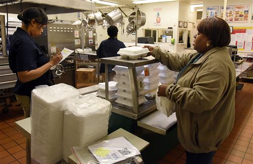Cafeteria worker hands a Styrofoam container to a woman.