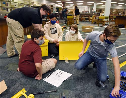 Man leans over pieces of a metal chest while 4 middle school students assemble it.