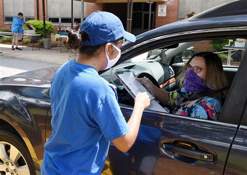 Woman in car wearing face mask receives a iPad from a young female teacher in blue T-shirt and ball cap.