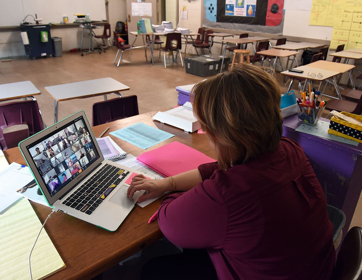 Teacher sits at her desk in an empty classroom during a Zoom meeting with students.