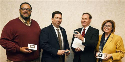 Three men and a woman pose while holding hotspot devices