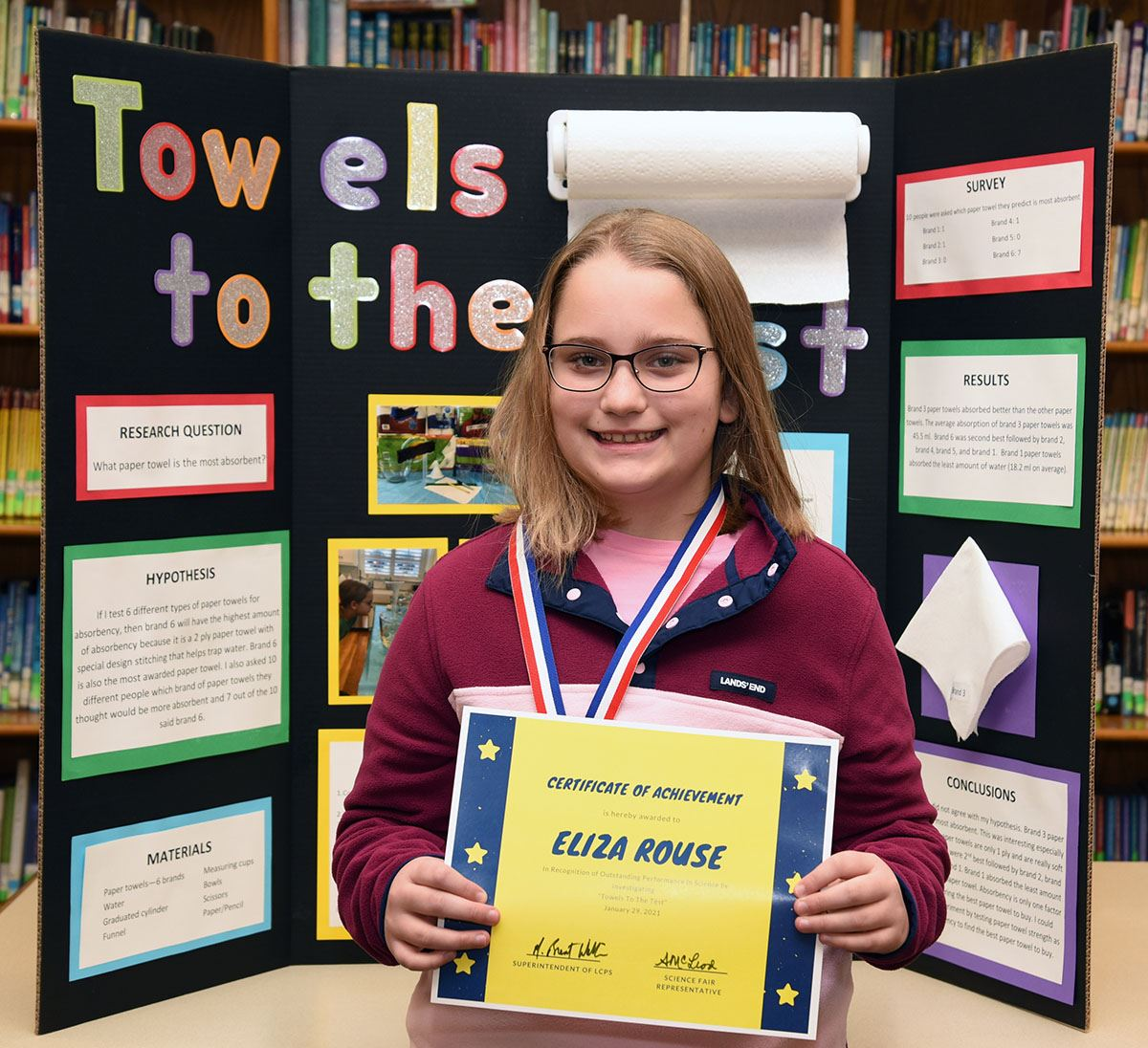 5th grade girls displays certificate as she stands before her Science Fair project.