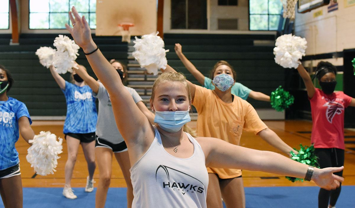 High school girls in face coverings practice cheerleading moves.