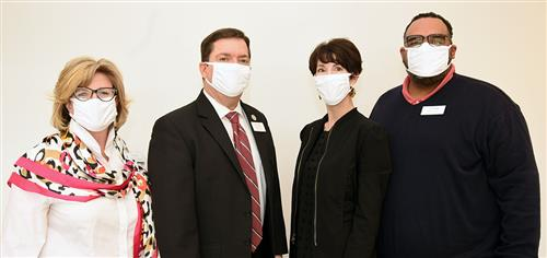 Four people -- two men and two women -- pose against a white wall wearing face masks.