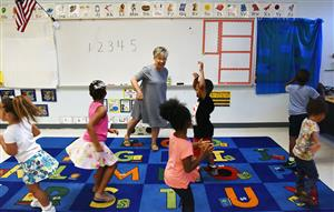Teacher Jo Pierce helps kindergarten students count to five as they spin in place.