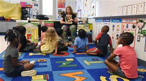 Kindergarten students sit on the carpet as teacher Katy Sowers prepares to read a book to them.