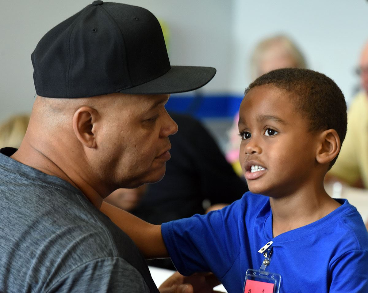 African American boy of kindergarten age talks with his grandfather.