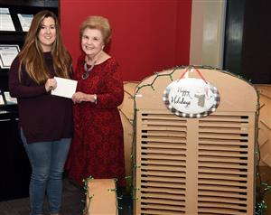 Older woman presents check to young female teacher.
