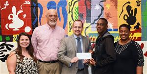 Reginald Dawson, second from right, an English teacher at North Lenoir High School, accepts a grant