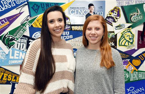 Two female high school senior pose in front of bulletin board decorated with college pennants.