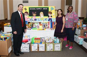 Man, at left, and two women flank a large display of school supplies