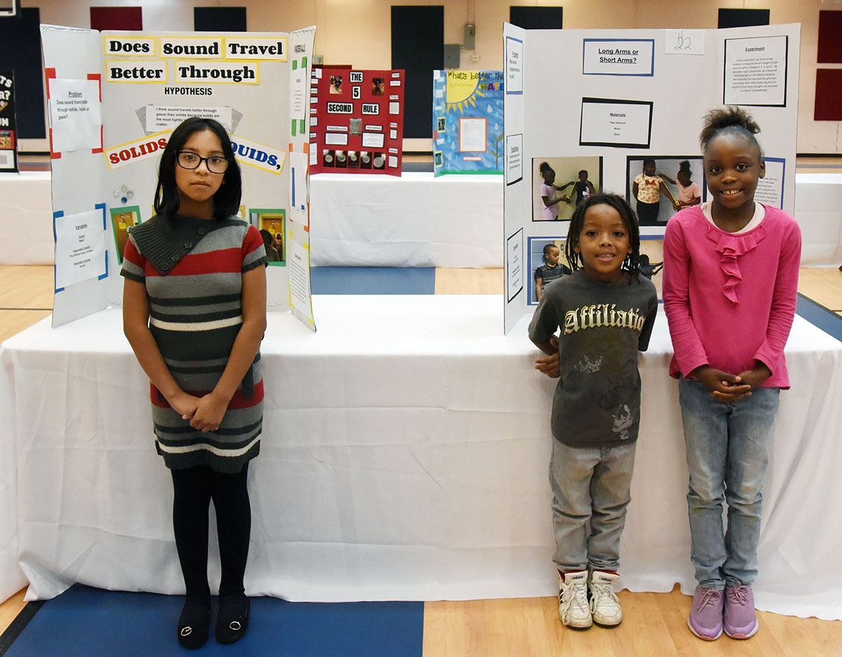 Three African American elementary students stand in front of their tri-fold science fair projects.