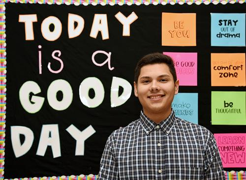 18-year-old Hispanic male poses in front of a colorful bulletin board at school.