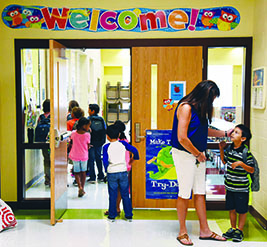 Teacher greets an elementary student in front of a Welcome sign.
