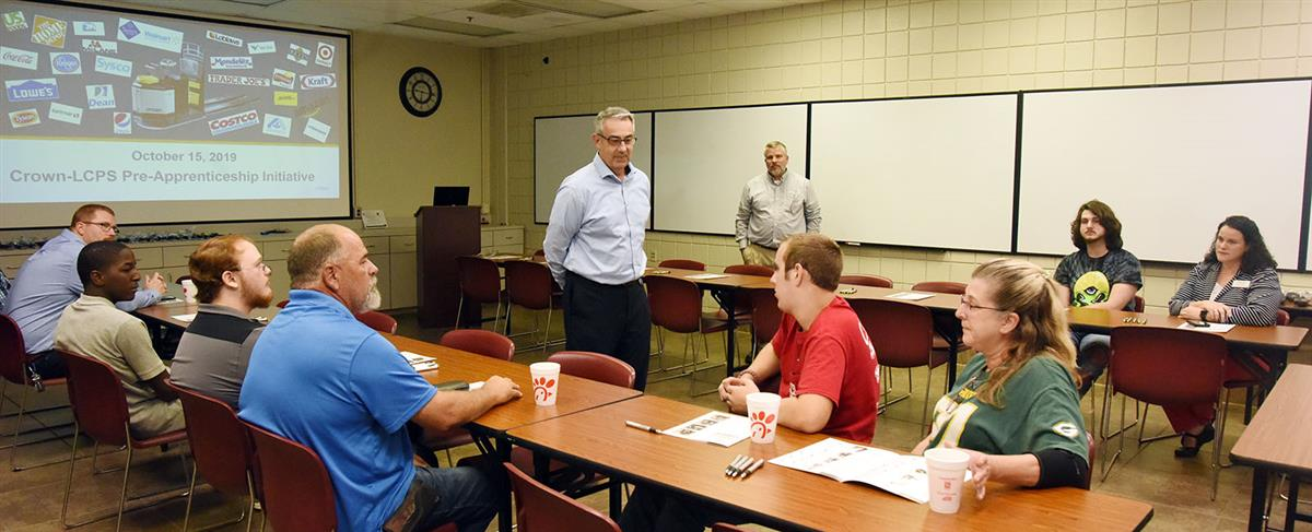 Man wearing glasses stand and talks to young male students and their parents who are seated at a table in a meeting room.