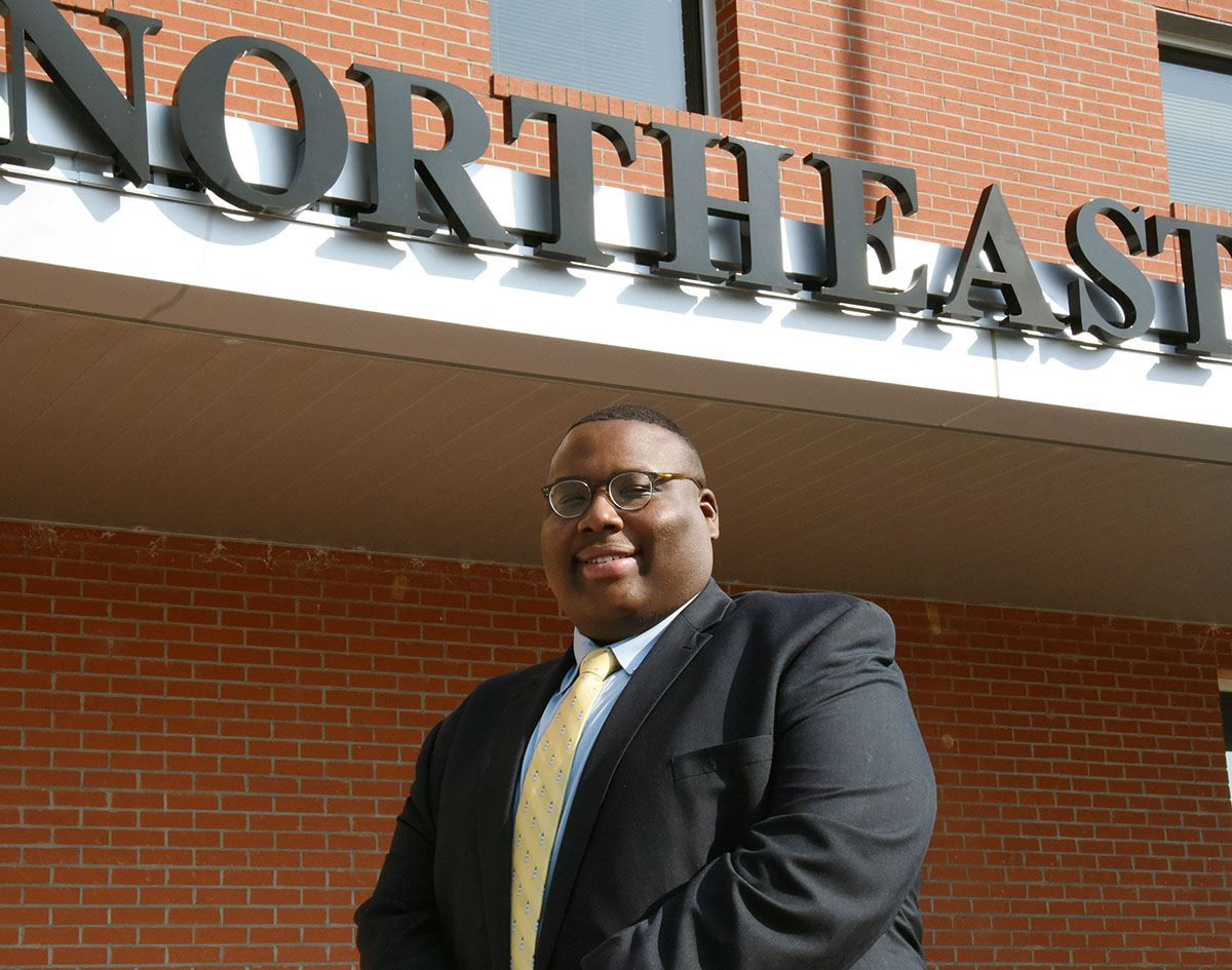 Rashard Curmon stands in front of Northeast Elementary sign