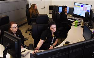 Two female students watch 911 call center workers do their job at computer monitors.