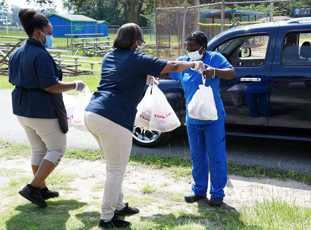 Two African American women in blue smocks hand plastic bags with meal containers to a third woman.